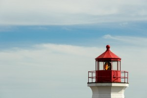 red lighthouse against blue sky and clouds
