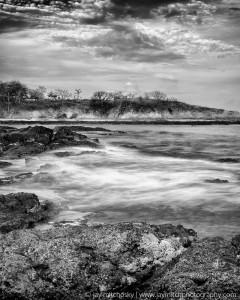 misty tide over rocky beach shore
